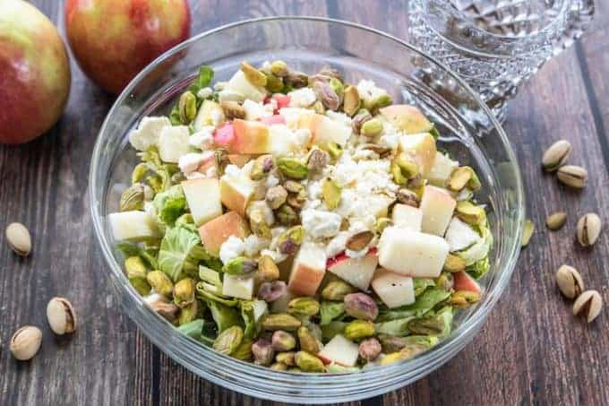 Brussels sprouts apple salad in a glass serving bowl topped with feta cheese.