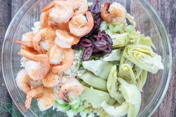 Greek Pasta Salad, a delicious recipe showing all the pasta ingredients including shrimp, olives, orzo, cucumber, dill, artichoke hearts and feta cheese in a large glass bowl on top of a wooden countertop.