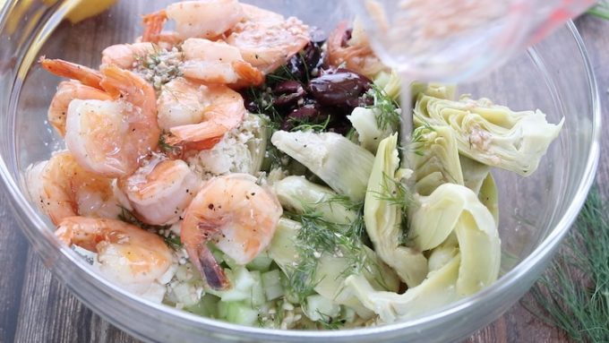 Greek Pasta Salad, a delicious recipe showing all the pasta ingredients including shrimp, olives, orzo, cucumber, dill, artichoke hearts and feta cheese in a large glass bowl on top of a wooden countertop with the dressing being poured over the top of the ingredients.