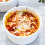 a microwave pizza is shown in a white ramekin with melted cheese and mini pepperonis.