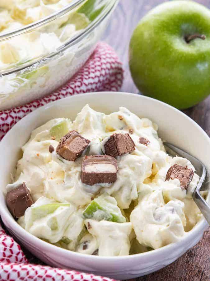 Fruit Salad with Cool Whip, a healthy dessert recipe being shown in a small white bowl with a metal fork on top of a red and white patterned towel with a green apple behind the bowl on the right and a large glass bowl with fruit salad on the left.