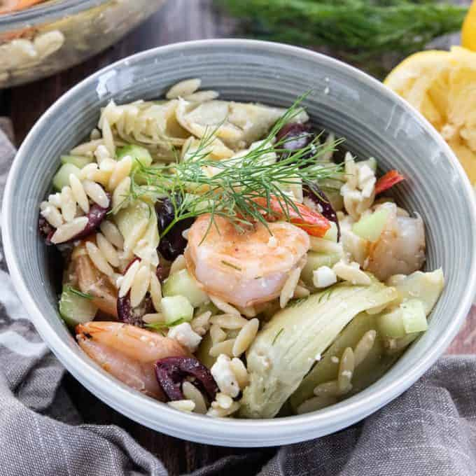 A bowl filled with orzo, shrimp, cucumbers, and artichokes.