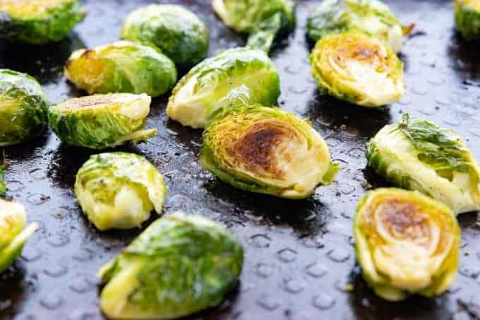 Baked Brussels sprouts, an oven roasted vegetable recipe being shown on a black baking sheet.