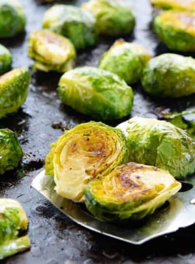 Roasted Brussels sprouts shown on a baking pan with a spatula taking some.