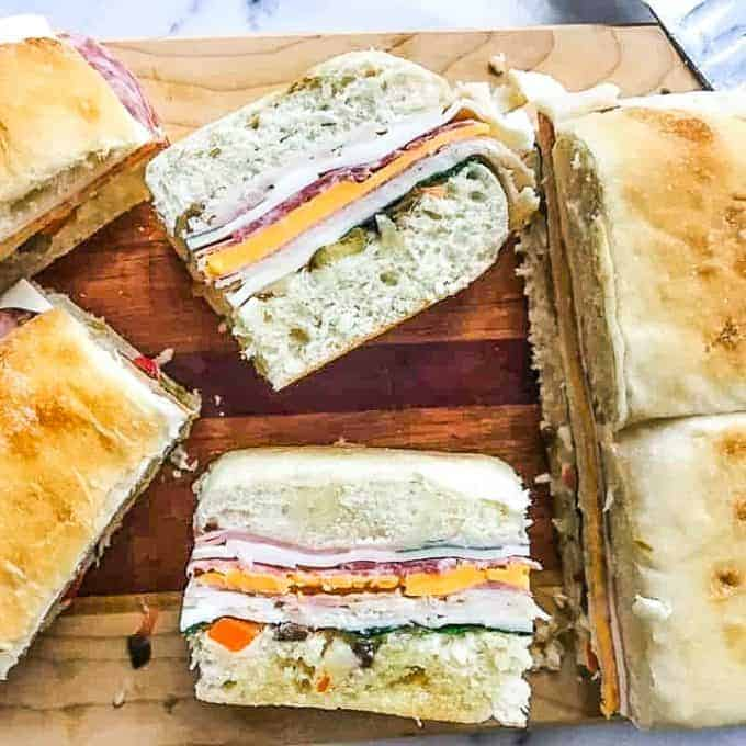 A piece of cake on a plate with a sandwich cut in half, with Muffuletta and Cheese