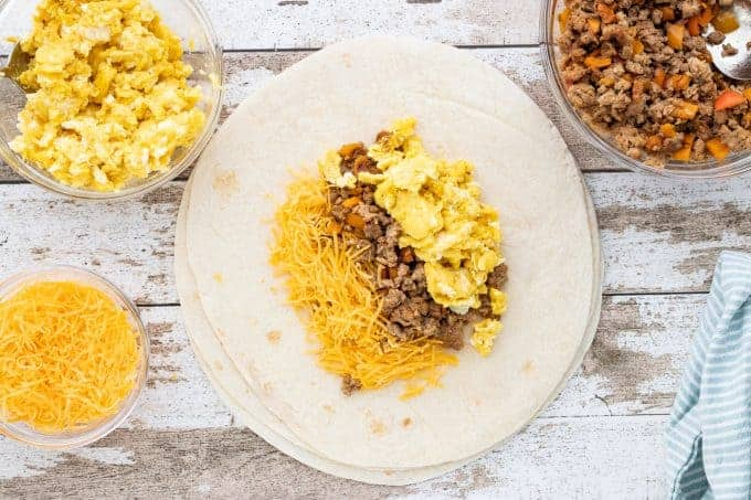 Breakfast Burrito, a freezer camping meal, showing a tortilla with cheese, ground pork and eggs in the middle with small glass bowls of shredded cheddar cheese, scrambled eggs and ground pork around the tortilla all on top of a wooden surface.
