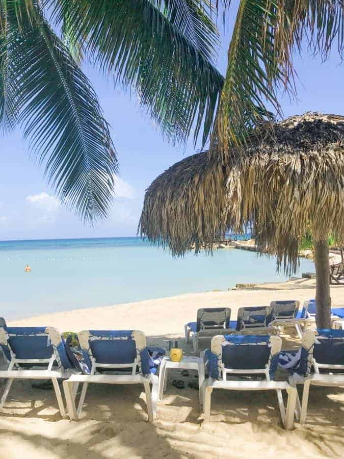 hilton rose hall jamaica beach showing the Caribbean Sea along with sand, beach chairs and a palm tree