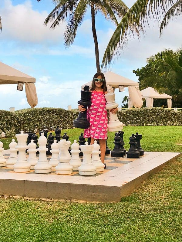 A girl standing on a life-size chess board at the hilton rose hall in jamaica