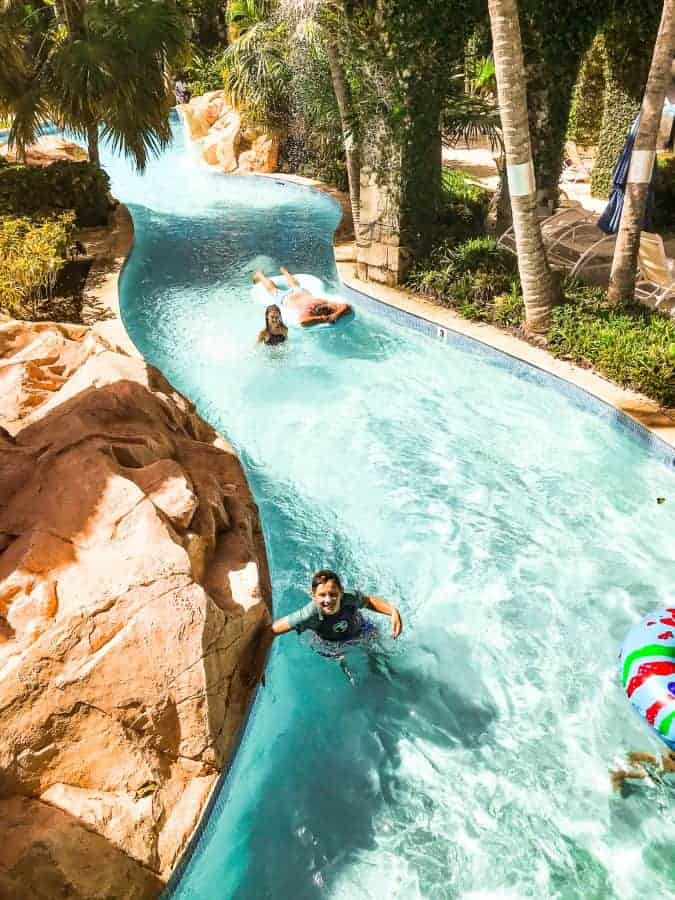 Hilton rose hall water park's lazy river with kids and adults floating on rafts