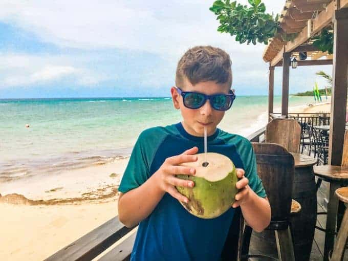 Hilton Rose Hall showing a boy drinking from a Coconut By the beach