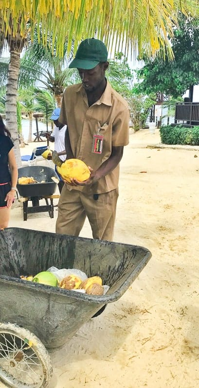 A man cutting open a coconut at Hilton rose hall jamaica