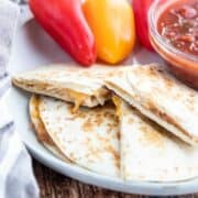 Camping Menu Ideas showcasing a Bean and cheese quesadilla on a white plate with salsa next to the plate.