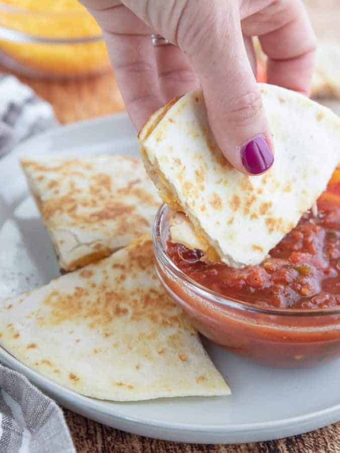 A person holding a piece of quesadilla diped in salsa