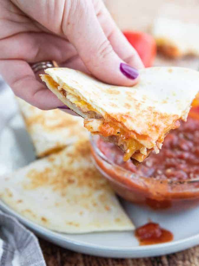 a slice of quesadilla dipped in salsa