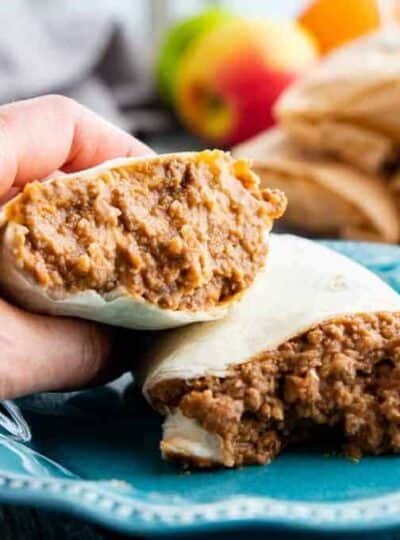 beef and beans wrapped in a tortilla cut in half with a hand holding one side on a blue plate.