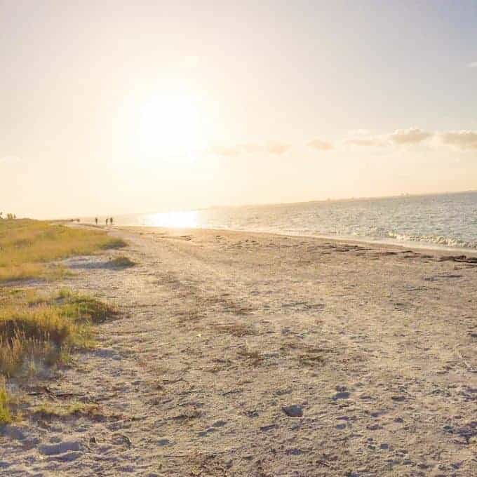 Beach photo of Sanibel Island showing the sun setting and people walking in the distance.