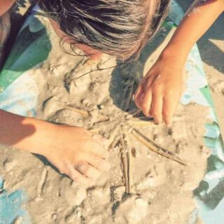 Girl uncovering a star fish on Sanibel Island Florida