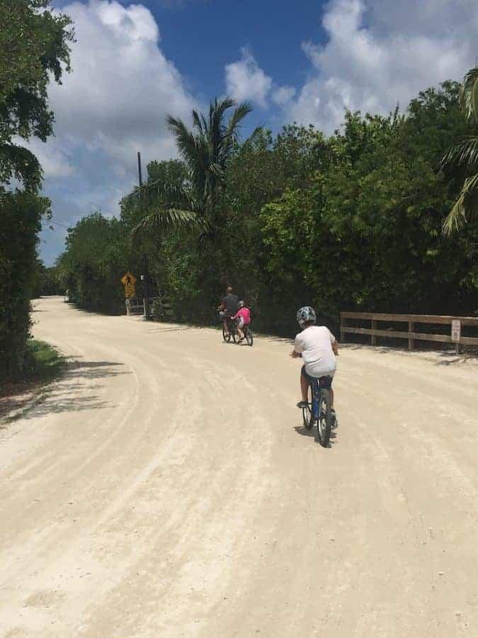 Family riding bikes on sand path in Sanibel Island florida