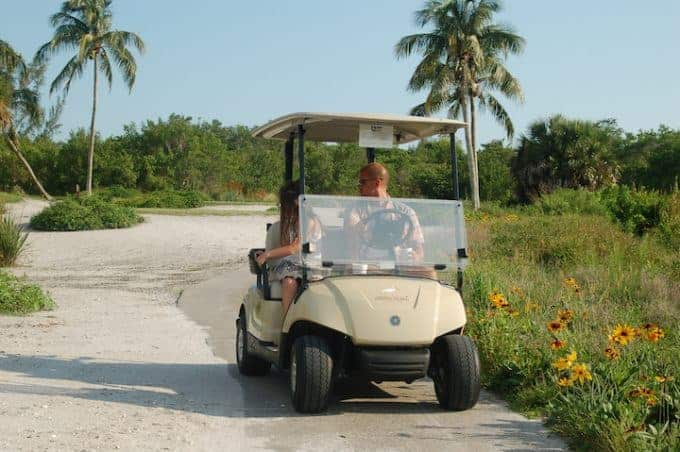 A dad and his daughter on a golf cart on Sanibel Island