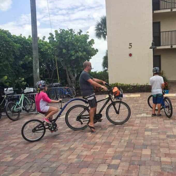 Dad with tandem bike with child in from of a hotel in Sanibel island Florida