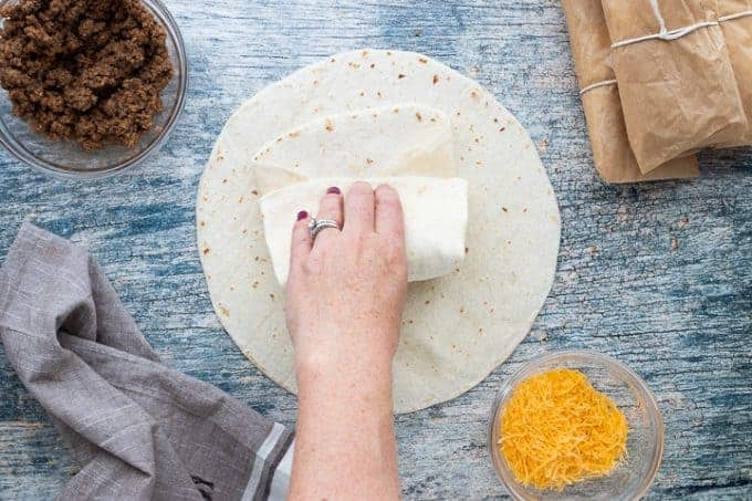 Beef and Cheese Burritos, a camping recipe showing a flour tortilla filled with ground beef and cheese being folded on top of a wooden surface with small glass bowls of ground beef, shredded cheese, wrapped burritos and a towel around the tortilla.