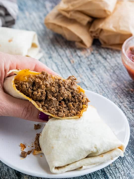 Beef and Cheese Burritos, a camping recipe showing a hand holding half of a cut burrito on a white plate with wrapped and unwrapped burritos behind the plate with a glass bowl of salsa all on top of a wooden surface.