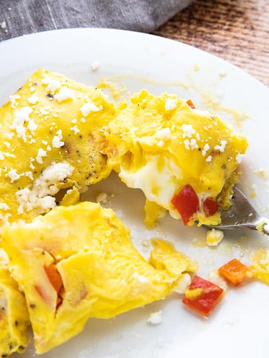 Boil in Bag Omelet, a camping recipe showing a cooked omelet with bell peppers, eggs, cheese and black pepper on a white plate on top of a wooden surface with a gray towel behind the plate.