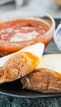 A tray of food on a plate, with Burrito and Refried beans