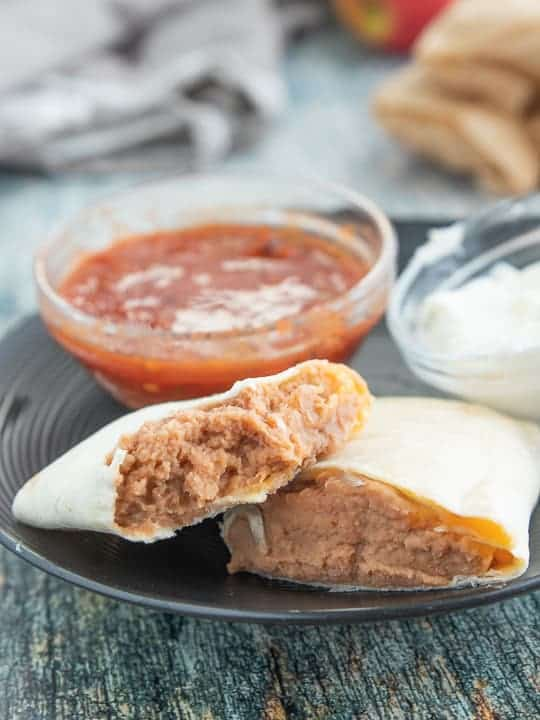 a bean burrito cut in half on a black plate with a small glass bowl of salsa and sour cream on the plate all on top of a wooden surface.