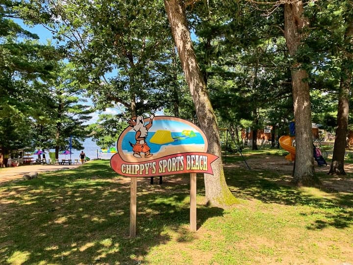 best camping in wisconsin showing chippy's sports beach with a playground and sand beach in the background.
