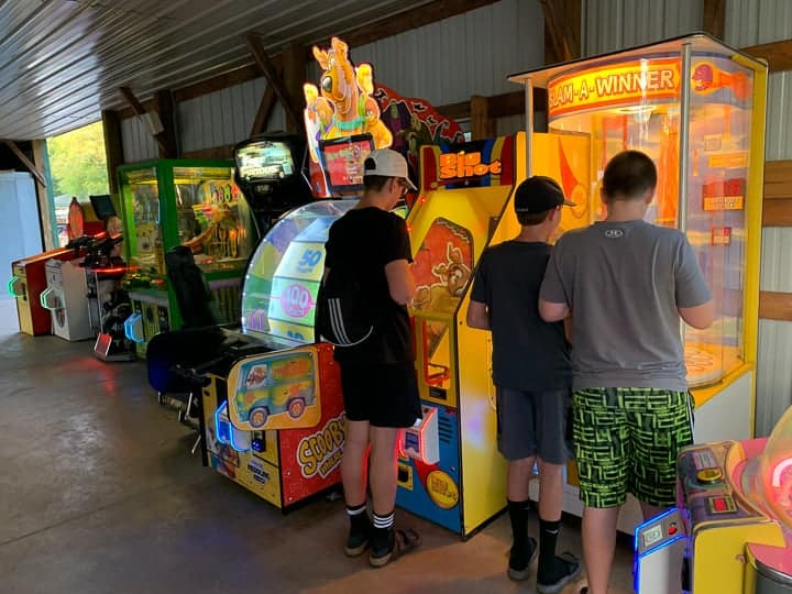 arcade at evergreen campground with 3 boys playing games.