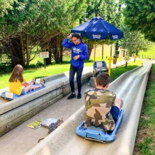 things to do in galena il showing the Alpine Slide at Chestnut mountain with 2 kids about to go down