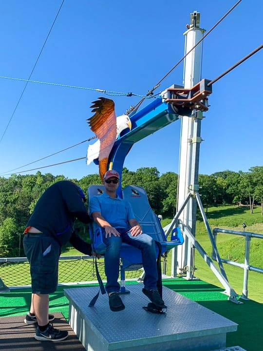 things to do in galena il showcasing a man getting onto the soaring Eagle Zipline