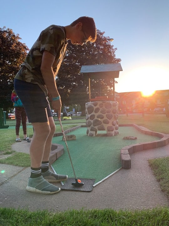 things to do in galena il showcasing a boy playing mini golf at sunset