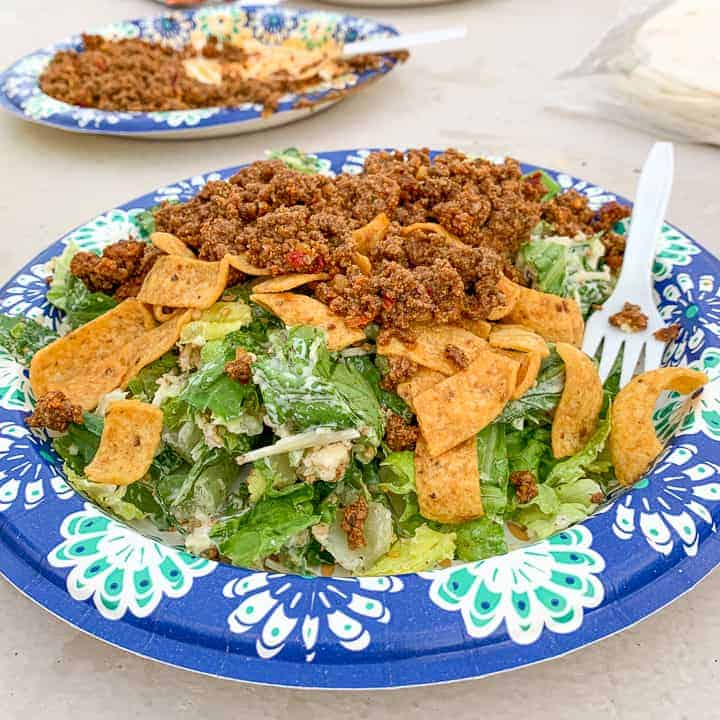 Camping Tacos shown on a paper plate with lettuce, Fritos, and taco meat.
