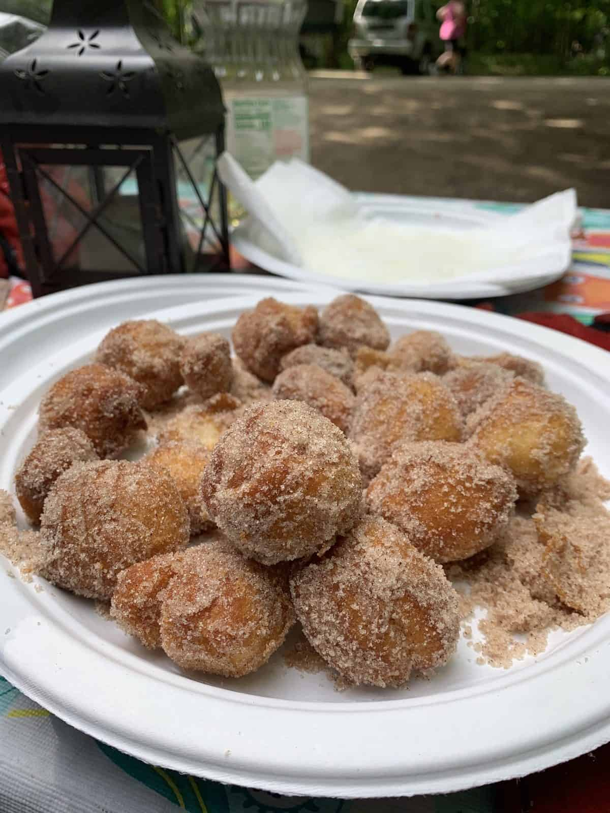 A paper plate loaded with homemade camping doughnuts covered in sugar and cinnamon.