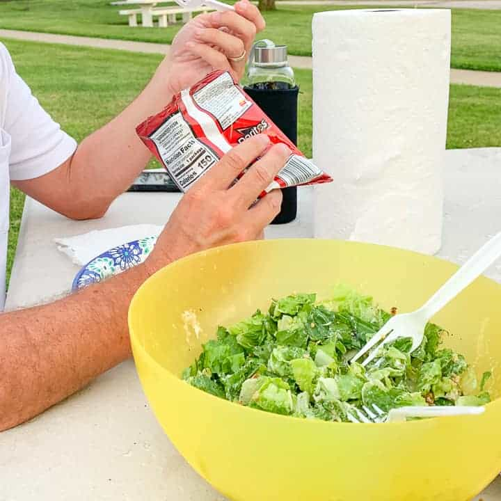 Doritos walking taco shown being held and eaten by a man with a salad on the table in front of him outside.