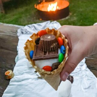 A girls hand is shown holding a waffle cone filled with marshmallows, m&ms, and chocolate bars with a sheet of tin foil on the picnic table behind her.