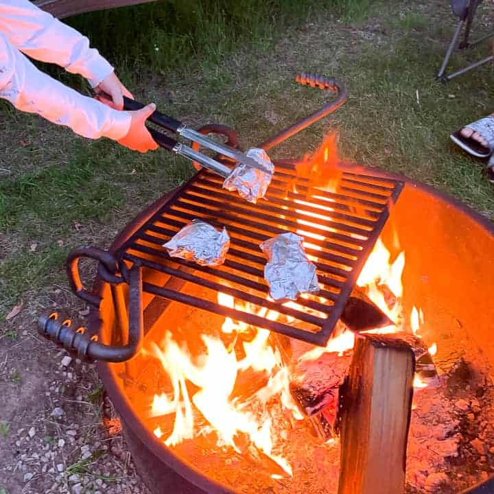 Campfire Dessert: Campfire Smores Cones are wrapped in foil and a Childs hands are carefully placing them on the campfire grate to cook.