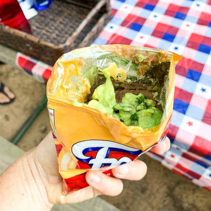 camping tacos shown in a Fritos bag with taco meat, refried beans, and guacamole.