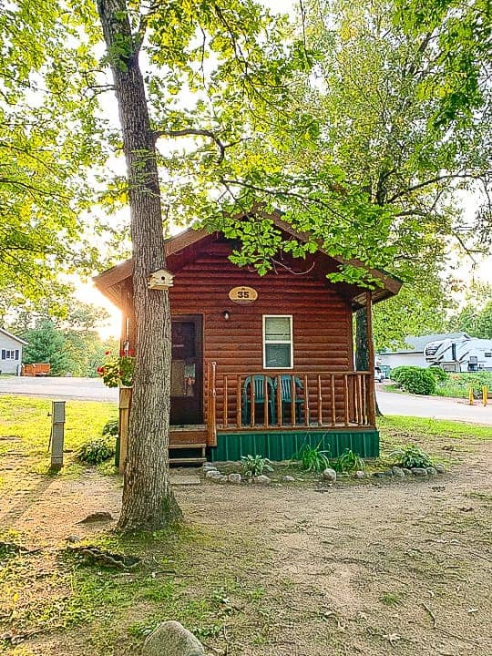 best camping in wisconsin at Evergreen campground in a standard cabin shown with trees surrounding the new looking small wooden cabin with a porch.