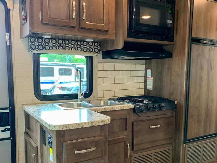 An RV kitchen with a stove and a microwave
