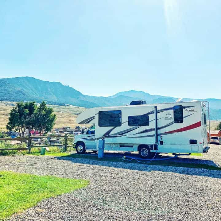 hilltop jayco RV shown in a campsite with mountains behind it.