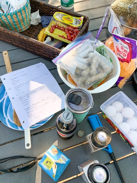 Camping menu shown on a picnic table next to breakfast items like sausage, eggs, and cheese.