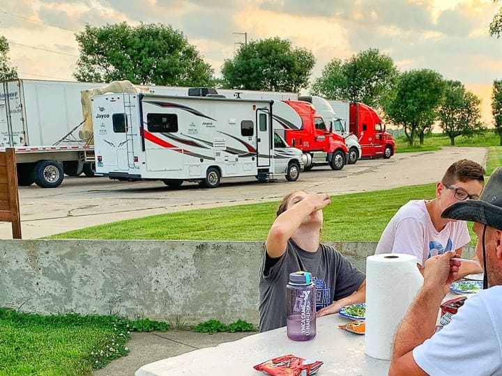 rv meals shown eaten at a rest stop picnic table with 3 people eating dinner.