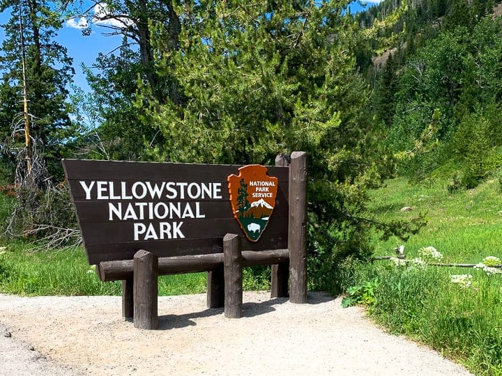 Yellowstone rv vacation showing the Yellowstone national park sign in front of woods.