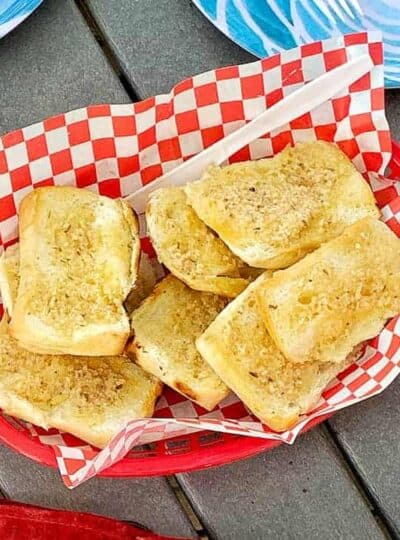 Garlic toast is in a red plastic serving bowl with red and white checkered paper on a picnic table.