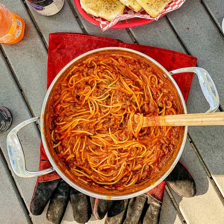 One pot camping meals: One pot spaghetti recipe shown in a stainless steel pot with a wooden spoon on top of large pot holders on a picnic table with garlic bread in the background.