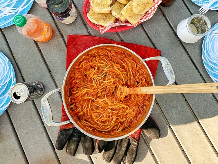 One pot camping meals: spaghetti shown in a stainless steel pot with a wooden spoon next to garlic bread on a picnic table.