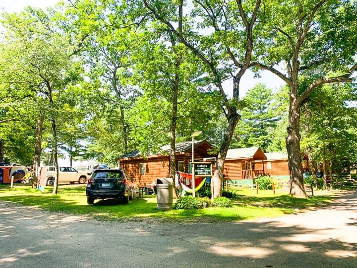 best camping in wisconsin showing some cabins and tree filled campsites at evergreen campground in wild rose, wi.